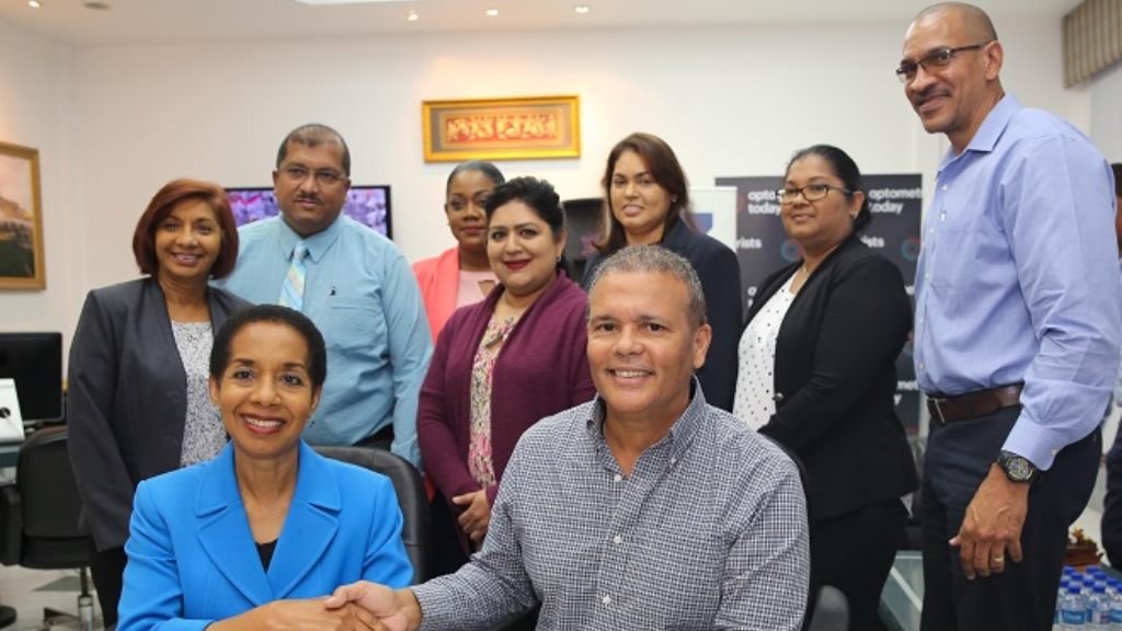 Massy Stores CEO (right, seated) Mr Derek Winford shakes hands with General Manager of Optometrist Today Theresa Alexis following the signing of an agreement to make hire purchase available to customers.