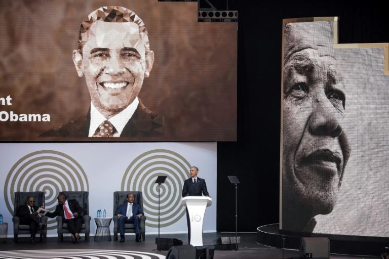 L'ex président américain Barack Obama, la veuve de Nelson Mandela, Graça Machel (à gauche) et le président sud-africain Cyril Ramaphosa (à droite) dansent en compagnie de la chanteuse Thandiswa Mazwai lors d'une cérémonie en l'honneur de Mandela, le 17 juillet 2018 à Johannesbourg