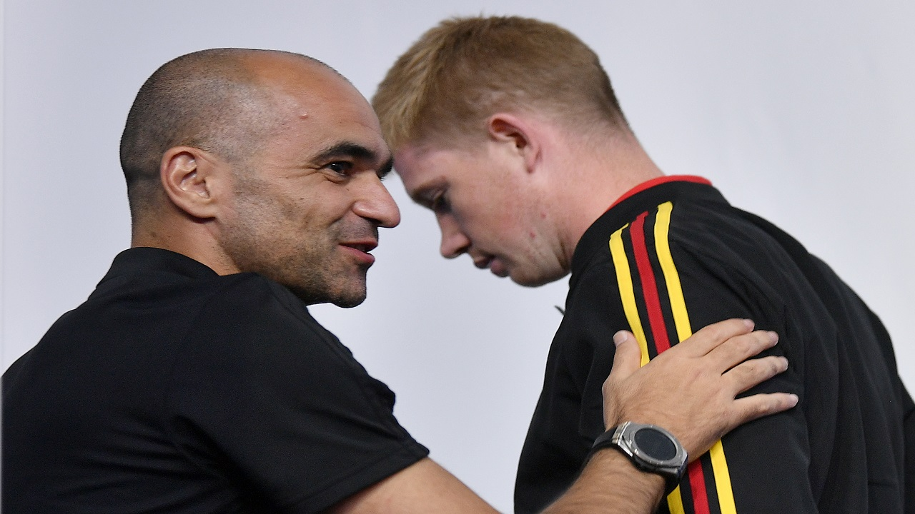 Belgium's Kevin De Bruyne leaves behind arriving Belgium coach Roberto Martinez during Belgium's official press conference on the eve of the semifinal match between France and Belgium at the 2018  World Cup in St Petersburg, Russia, Monday, July 9, 2018. (AP Photo/Martin Meissner)