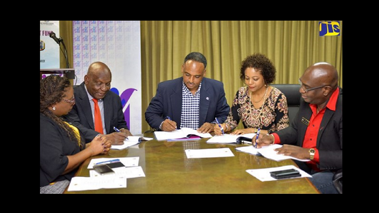AG and MP for James West Central, Marlene Malahoo Forte (second right), and Managing Director, JSIF, Omar Sweeney (centre), sign contracts for JSIF's 2018 summer camps, at the agency's Oxford Road offices in St. Andrew on July 27. Others participating in the signing (from left) are Social Development Manager, JSIF, Mona Sue-Ho; Executive Director, Operation Friendship, Rev. Dr. Webster Edwards; and Acting Assistant Commissioner of Police, Steve McGregor. (Photo: JIS)