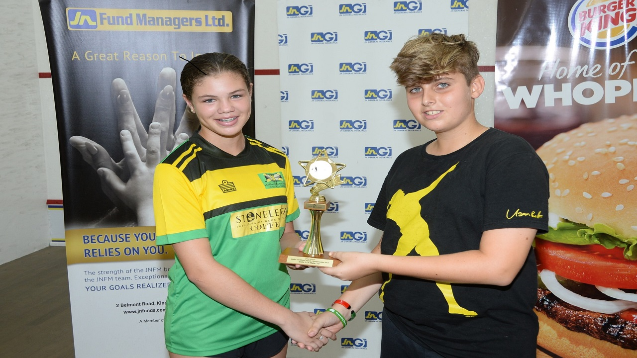 Jamaica's Savannah Thomson, (left) who won the Girls' Under 13  title at the 2018 JN General Insurance Caribbean Area Squash Association's (CASA) Junior Championships, accepts her trophy from Tobias Levy, representing his father, Bruce Levy, who is a partner of Levy Cheeks during the awards ceremony on the final day of the championships on Saturday the Liguanea Club in New Kingston.