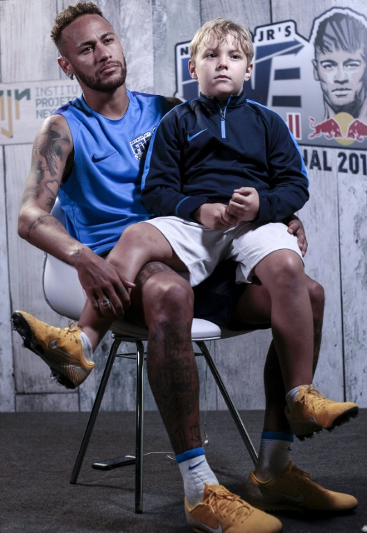 Neymar, avec son fils Davi Lucca, accorde un entretien à l'AFP, le 21 juillet 2018 à Praia Grande, près de Sao Paulo