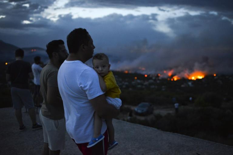 Des Grecs observent un feu de forêt à Rafina dans la banlieue d'Athènes, en Grèce