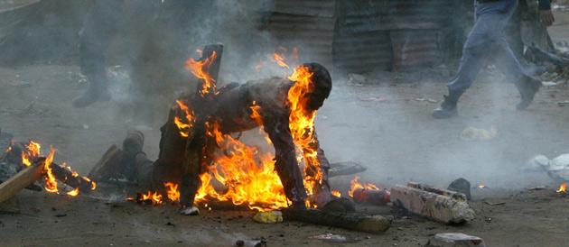 Photo Illustration: AFP (des policiers sud-africains viennent au secours d'un homme immolé par des agresseurs, le 18 mai 2008 à Johannesbourg)
