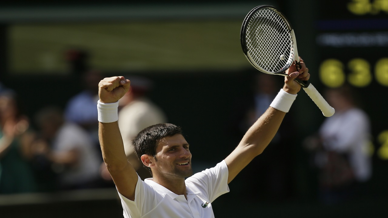 Novak Djokovic of Serbia celebrates defeating Kei Nishikori of Japan during their men's quarterfinal match at the Wimbledon Tennis Championships in London, Wednesday July 11, 2018. (AP Photo/Tim Ireland).