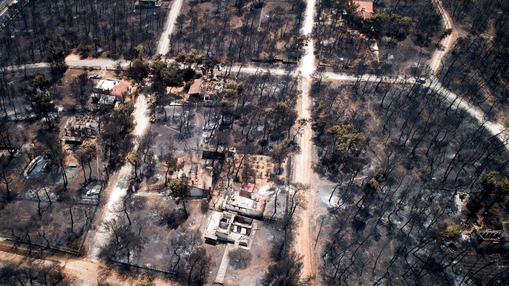 This Wednesday, July 25, 2018 aerial photo shows burnt houses and trees following a wildfire in Mati, east of Athens. Frantic relatives searching for loved ones missing in Greece's deadliest forest fire in decades headed to Athens' morgue on Thursday, July 26, 2018 as rescue crews and volunteers continued searches on land and at sea for potential further victims. (Antonis Nikolopoulos/Eurokinissi via AP)