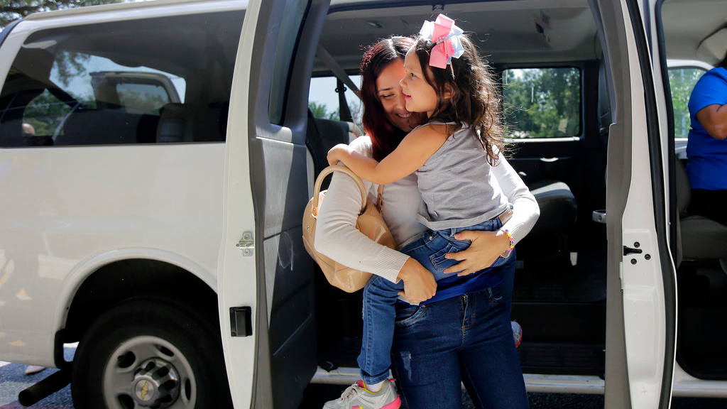 Immigrants from Brazil seeking asylum, Natalia Oliveira da Silva carries her daughter, Sara, 5, from a van as they arrive at a Catholic Charities facility, Monday, July 23, 2018, in San Antonio. (AP Photo/Eric Gay)