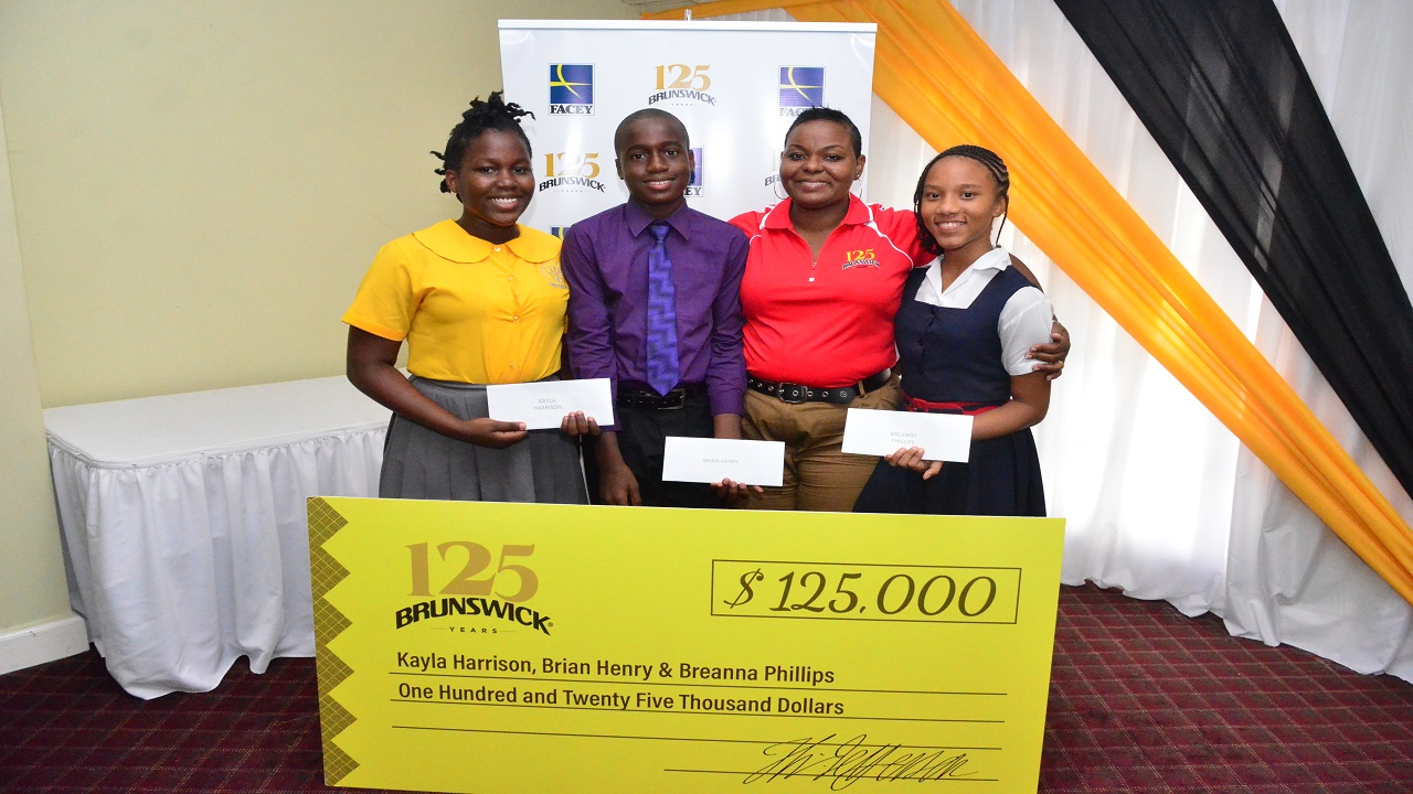 Simone McFarlane, Brand Manager, Brunswick celebrates with the first Brunswick GSAT Scholars (Left to right)  Kayla Harrison, Greater Portmore Primary, Brian Henry, Excelsior Primary, and Breanna Phillips, Unity Primary at the GSAT Awards Luncheon at the Four Season Hotel on Monday.
