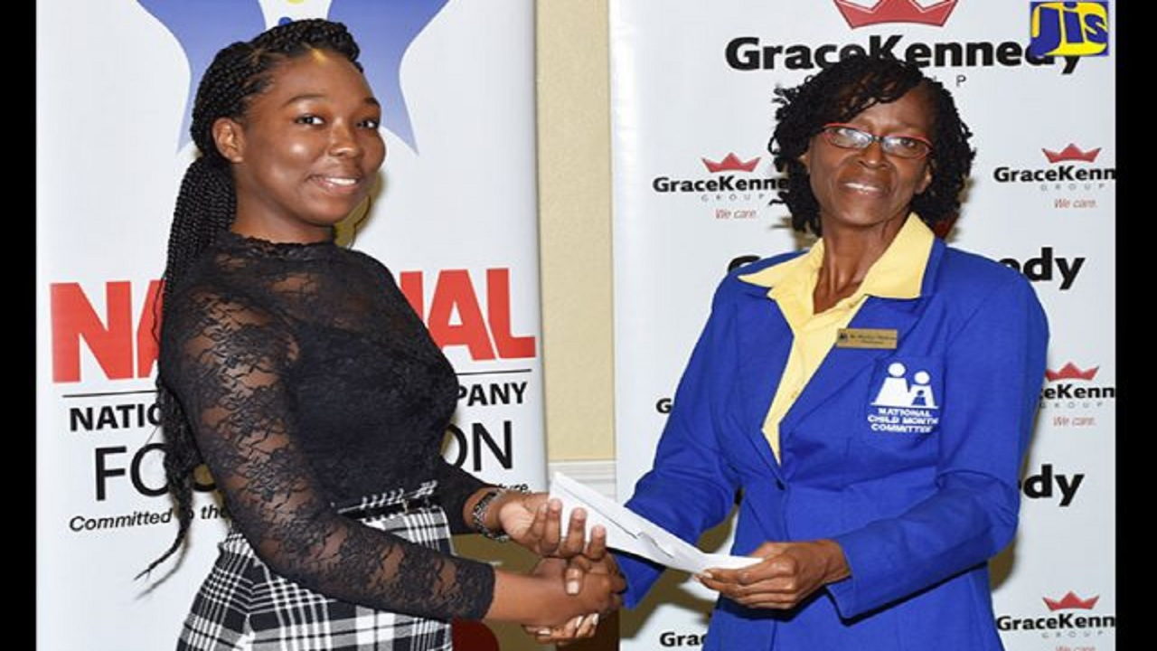 Top student for the National Child Month Committee's (NCMC) 2018 Youth Academic Achievement Awards, Britney Huie (left), receives her award from NCMC Chairperson, Dr. Pauline Mullings, during the presentation ceremony at Knutsford Court Hotel, New Kingston on June 27.