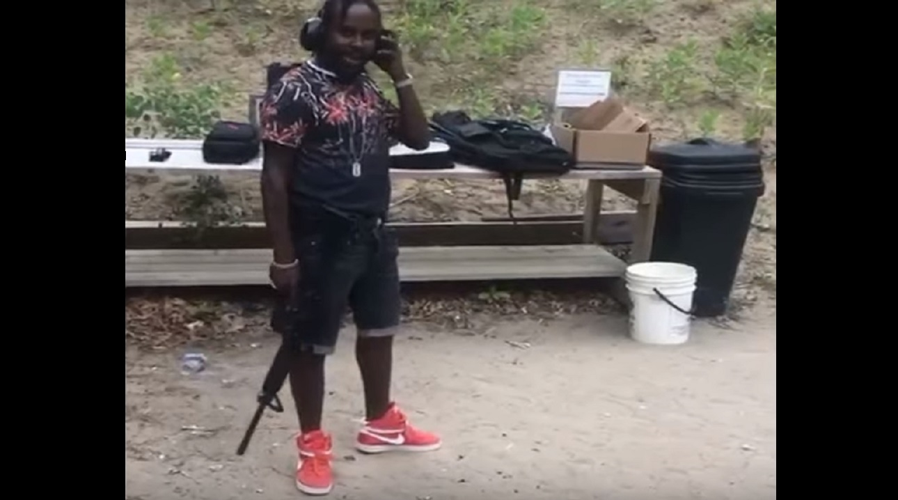 Screenshot of a video showing Popcaan with a gun at a range in Canada.