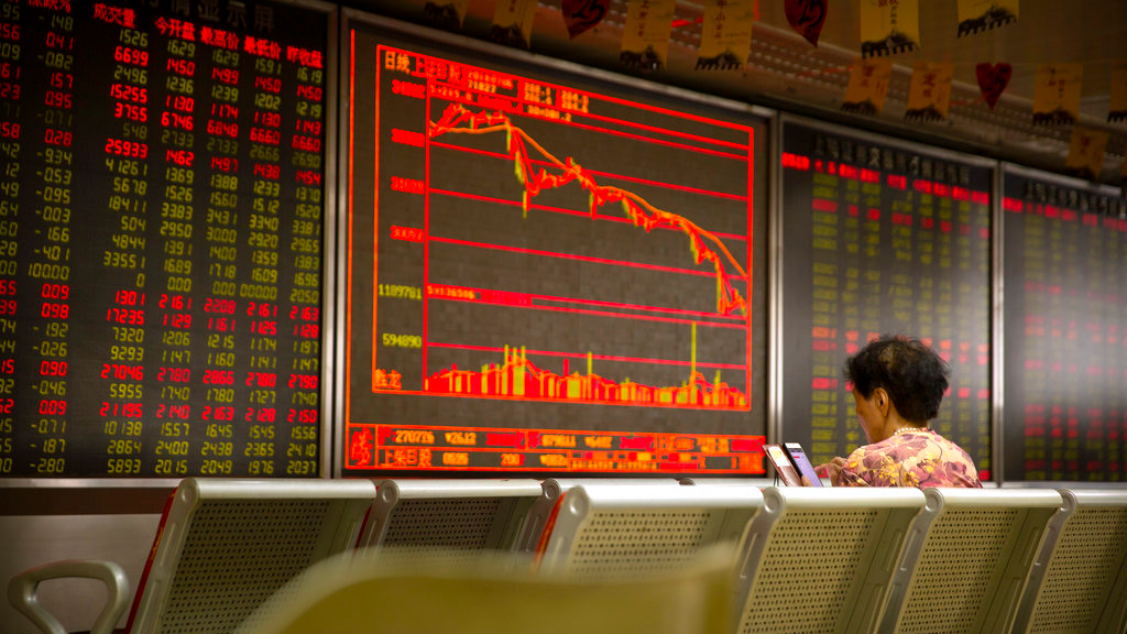 A Chinese investor uses her smartphone as she monitors stock prices at a brokerage house in Beijing, Friday, July 6, 2018. (AP Photo/Mark Schiefelbein)