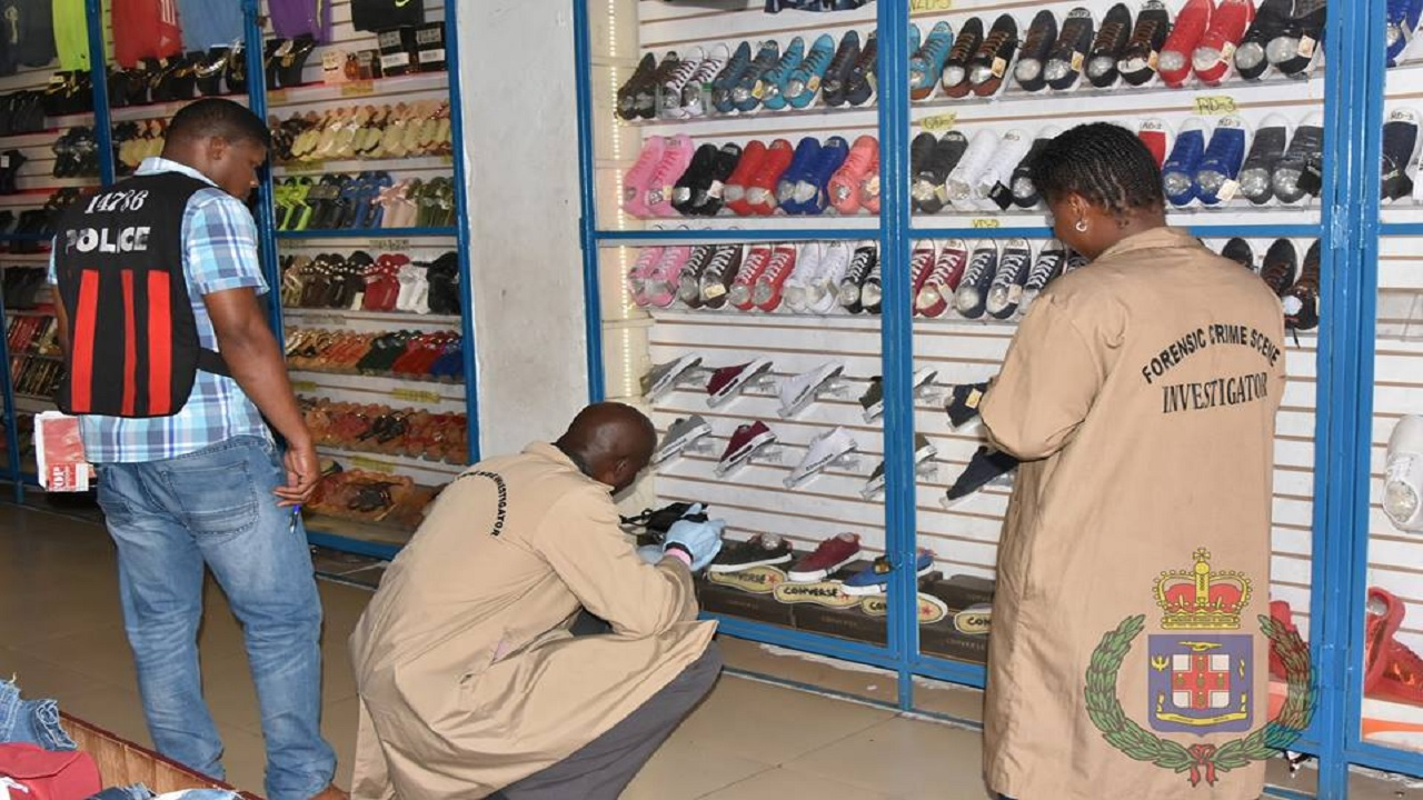 Police investigators examine goods in search of counterfeit merchandise at a store in downtown Kingston during a raid at the establishment earlier this year.