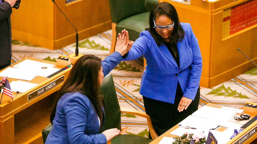 In this Jan. 9, 2017 file photo, Rep. Teresa Alonso Leon and Rep. Janelle Bynum, right, high-five after members of the House of Representatives are sworn into office at the Oregon State Capitol in Salem, Ore. A black Oregon lawmaker says one of her constituents called police as she canvassed a Portland-area neighborhood that she represents.
