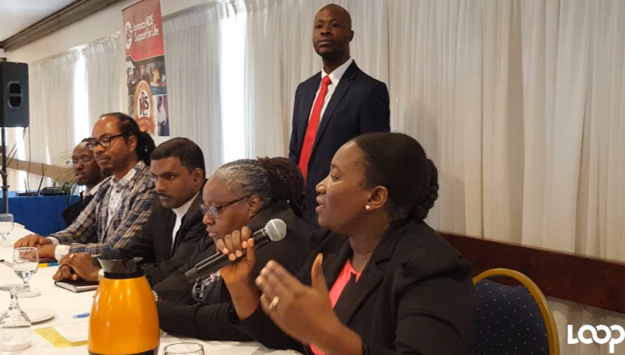 Kandasi Levermore (right), executive director of Jamaica AIDS Support for Life, addresses audience members during a panel discussion at the HIV symposium.