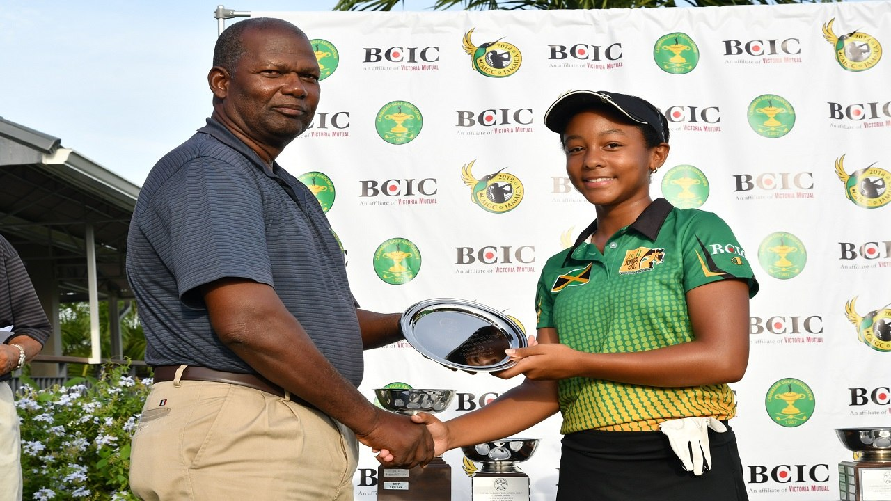 Trenton Weekes, Secretary of the Caribbean Golf Association hands Emily Mayne her 2nd place trophy for the girls 13 & Under competition.