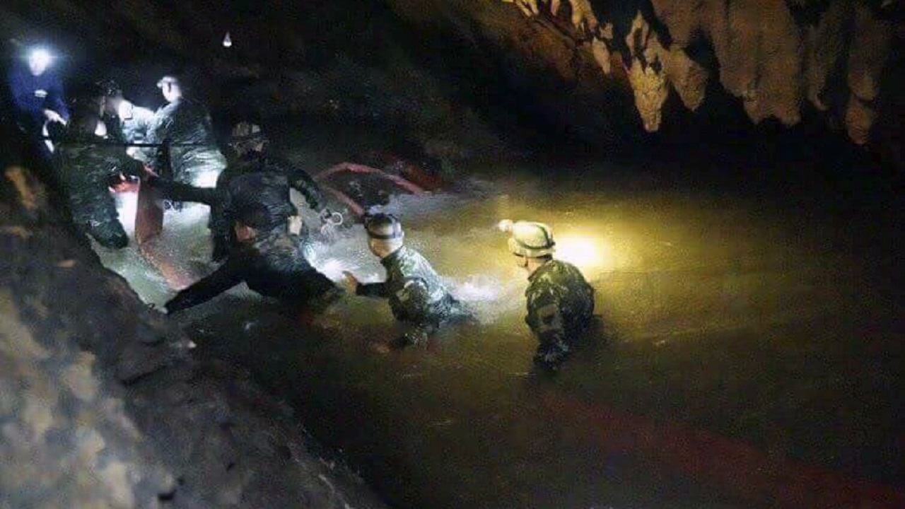(Image: AP: Thai rescue teams walk inside the cave complex on 2 July 2018)