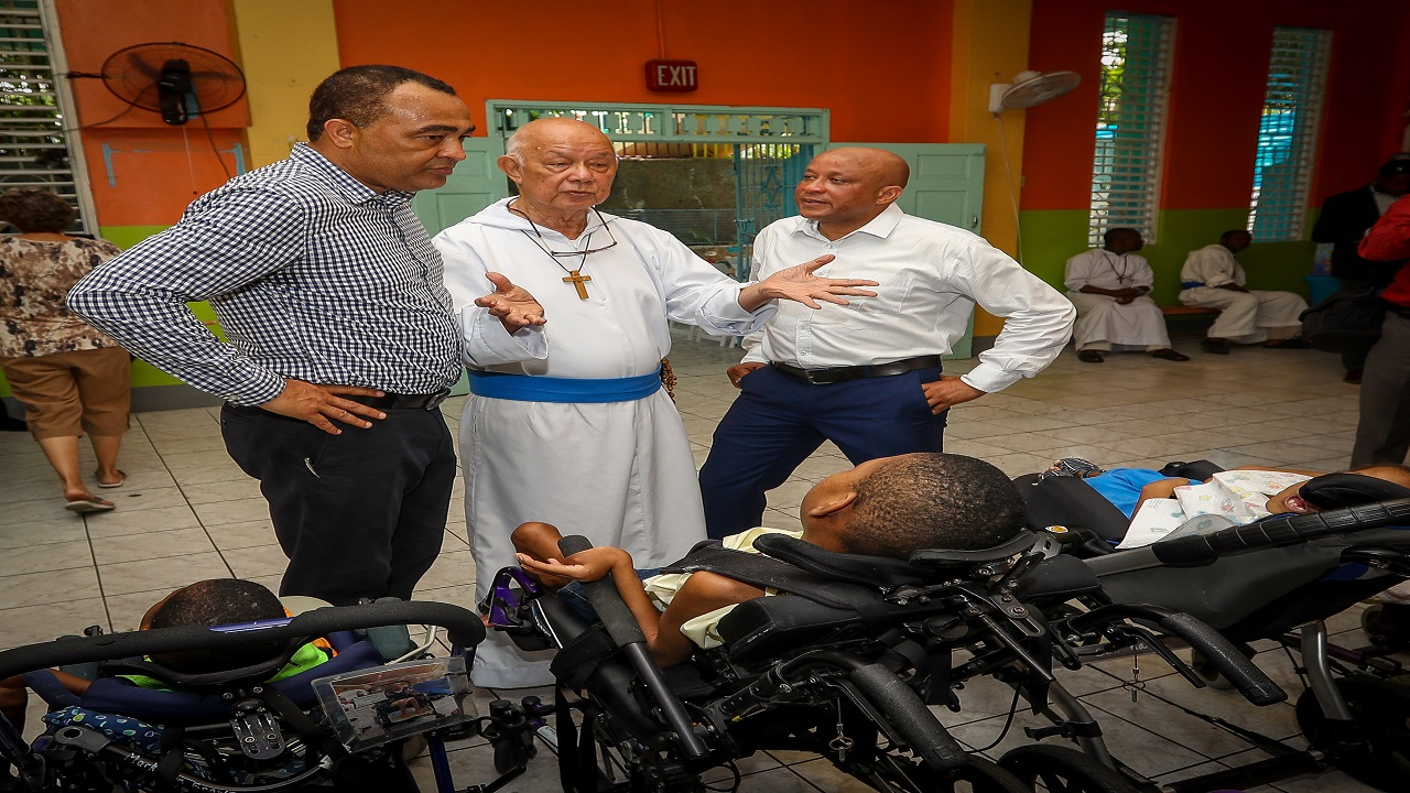 Father Richard Ho Lung (centre), speaks with Minister of Health Dr Christopher Tufton (left) and Executive Vice President of Individual Life Insurance at Sagicor, Mark Chisholm (right).