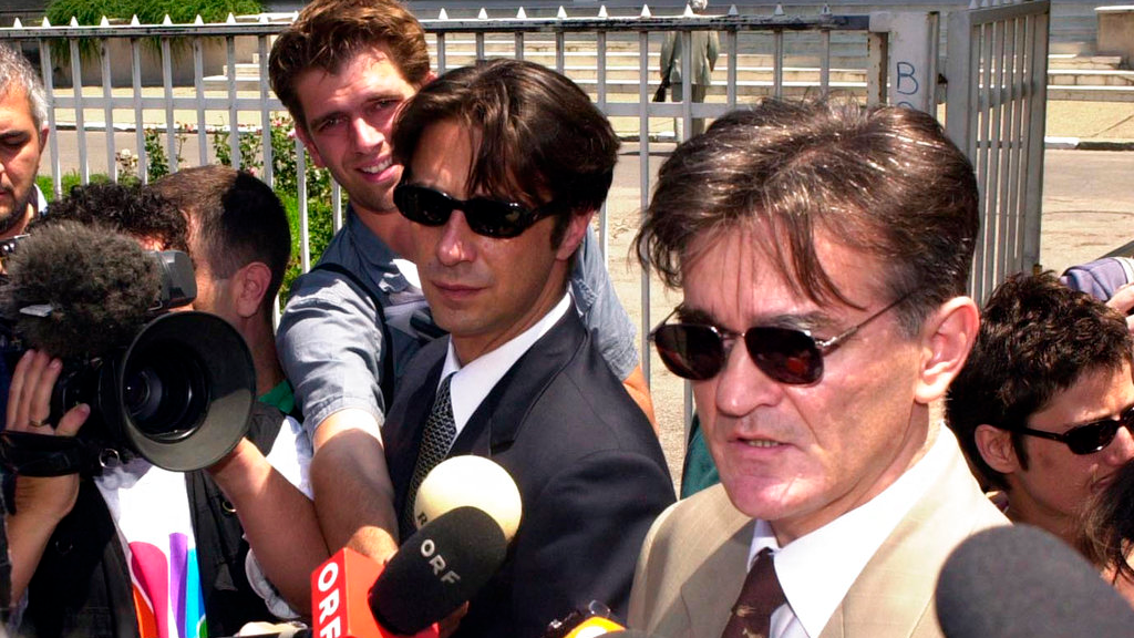 FILE - In this Wednesday June 27, 2001 file photo, Former Yugoslav President Slobodan Milosevic's lawyers Dragoslav Ognjanovic, center, and Zdenko Tomanovic, right, address media after the team visited imprisoned Milosevic in Belgrade. Serbian police say that a prominent lawyer, who helped defend former strongman Slobodan Milosevic before the Yugoslav war crimes tribunal, has been shot and killed. (AP Photo/Darko Vojinovic, file)