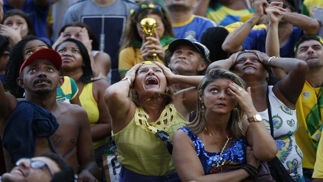 Brazil football fans cry out as they watch their team lose 2-1 to Belgium in a World Cup quarter final match, on a live telecast, in Rio de Janeiro, Brazil, Friday, July 6, 2018. Belgium knocked Brazil out of the World Cup and advanced to the semi-finals. (AP Photo/Silvia Izquierdo).
