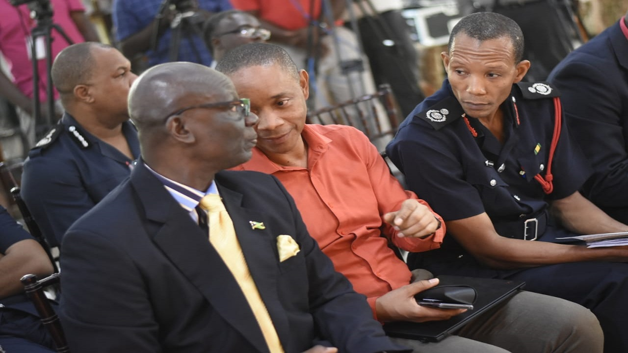 NSWMA chairman Dennis Chung (centre) makes a point in discussion with Local Government Minister Desmond McKenzie (left) while Stewart Beckford of the Jamaica Fire Brigade looks on. (PHOTOS: Marlon Reid)