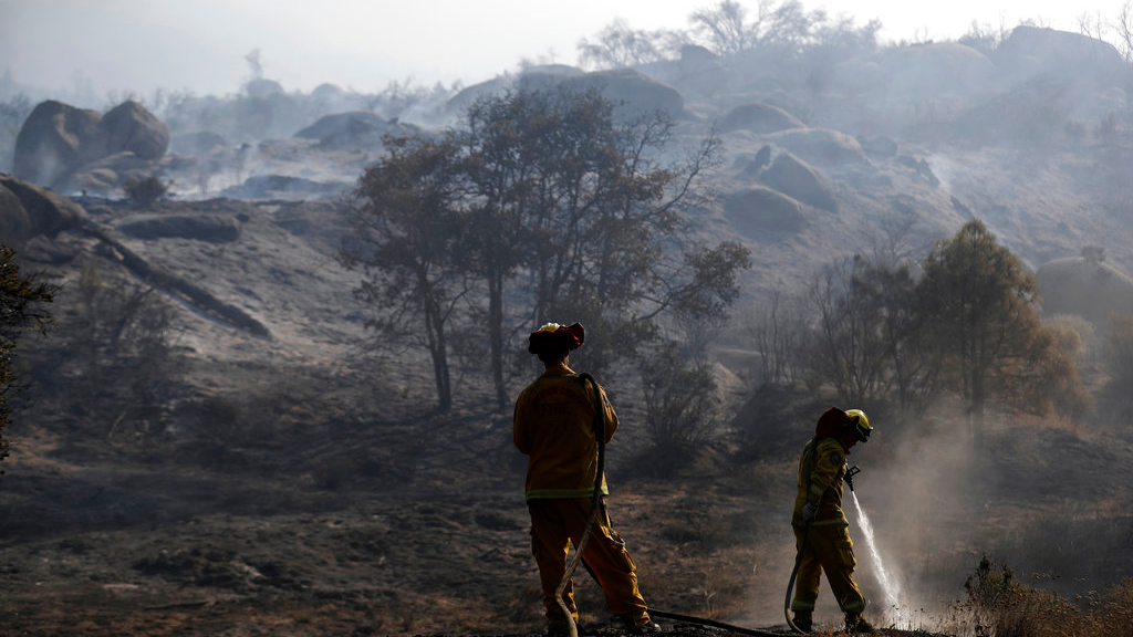Firefighters hose down hot spots along Highway 243 on Thursday, July 26, 2018, near Idyllwild, Calif. A fast-moving wildfire tore through trees, burned several homes and forced evacuation orders for an entire mountain town as California sweltered under a heat wave and battled ferocious fires at both ends of the state. (AP Photo/Marcio Jose Sanchez)