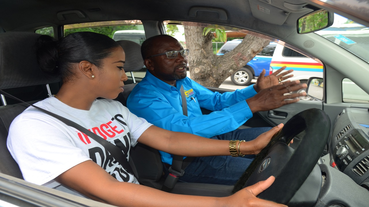 Tyheissa Williams, Red Stripe's Communication and Sustainability Executive, pays keen attention to Alphonso Grennell, Managing Director of Grennell's Driving School, as he instructs her in a defensive driving session.