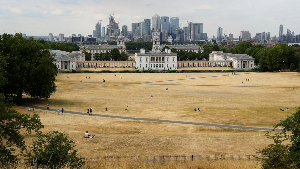 A view shows parched grass from the lack of rain in Greenwich Park, backdropped by the Royal Museums Greenwich and the skyscrapers of the Canary Wharf business district, during what has been the driest summer for many years in London, Tuesday, July 24, 2018. Britain is experiencing a severe heatwave which has prompted its national weather service to issue an alert for people to 'stay out of the sun'. (AP Photo/Matt Dunham)