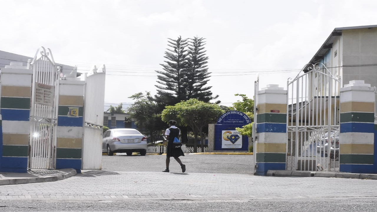 A student is pictured entering the Meadowbrook High School compound in St Andrew on Tuesday. (PHOTOS: Marlon Reid)