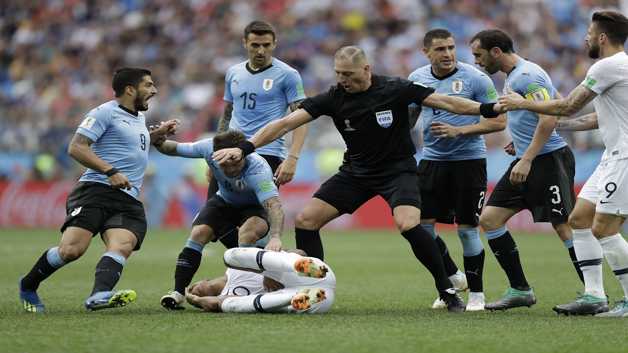 Uruguay players protest to referee Nestor Pitana of Argentina that France's Kylian Mbappe, on the ground, is overreacting after taking a dive during their quarterfinal match  at the 2018 football World Cup in the Nizhny Novgorod Stadium, in Nizhny Novgorod, Russia, Friday, July 6, 2018. (AP Photo/Natacha Pisarenko).