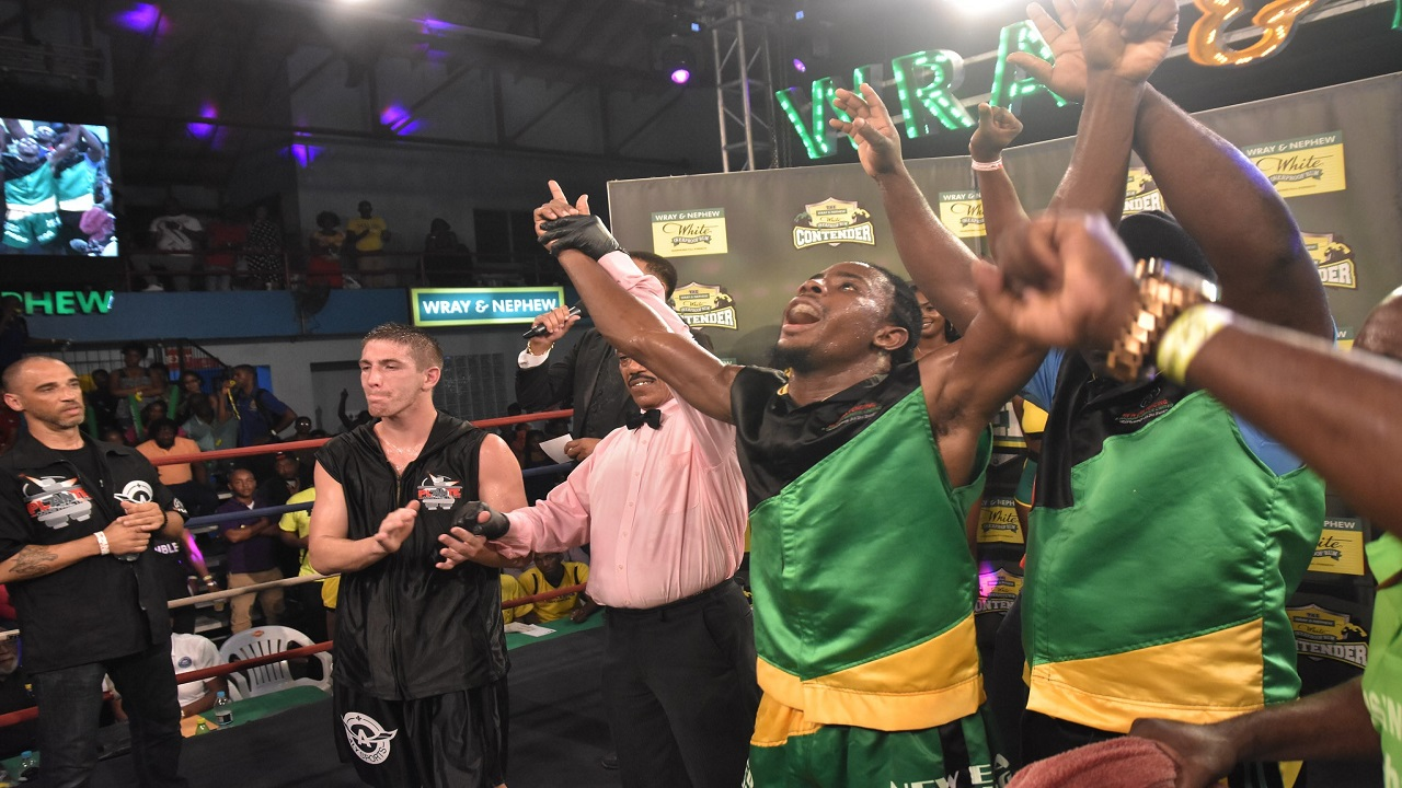 Jamaica's Richard 'Frog' Holmes (right) celebrates after being declared the winner, by split decision, of the first semi-final bout of the  Wray & Nephew Contender welterweight competition over Canada's Dave Leblond, at the Chinese Benevolent Association last week Wednesday.