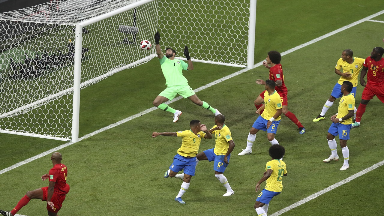 Brazil goalkeeper Alisson, center, fails to stop Belgium's first goal during the quarterfinal match at the 2018 football World Cup in the Kazan Arena, in Kazan, Russia, Friday, July 6, 2018. (AP Photo/Thanassis Stavrakis).