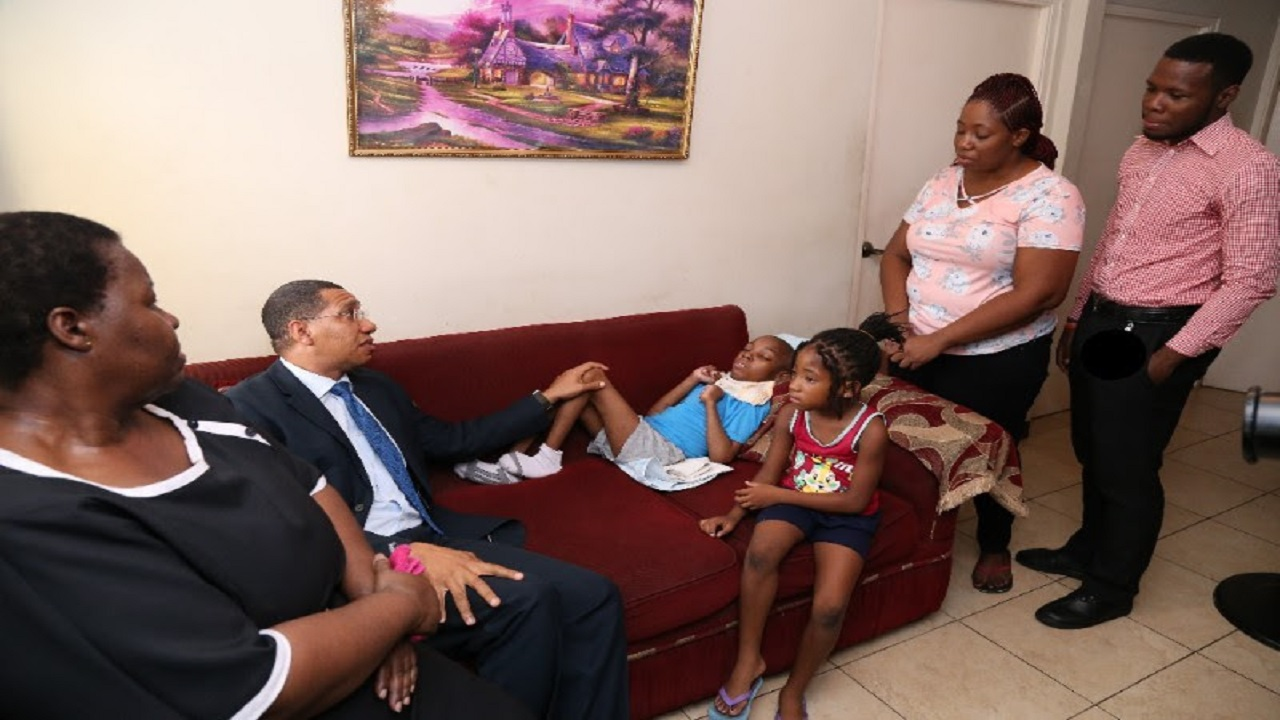Prime Minister Andrew Holness visits Tahj Rowe and his family Tuesday to make a personal donation.  (PHOTO: OPM)