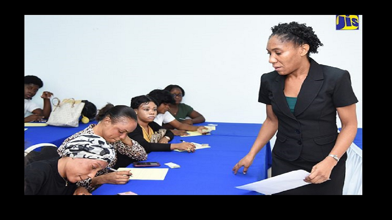Acting Director, Electronic Labour Exchange Department in the Ministry of Labour and Social Security, Dahlia Green (right), observes as young people from Denham Town, Kingston, complete a form. Occassion was an orientation session on Wednesday (July 4) at Medallion Hall Hotel in St. Andrew. Photo: JIS.