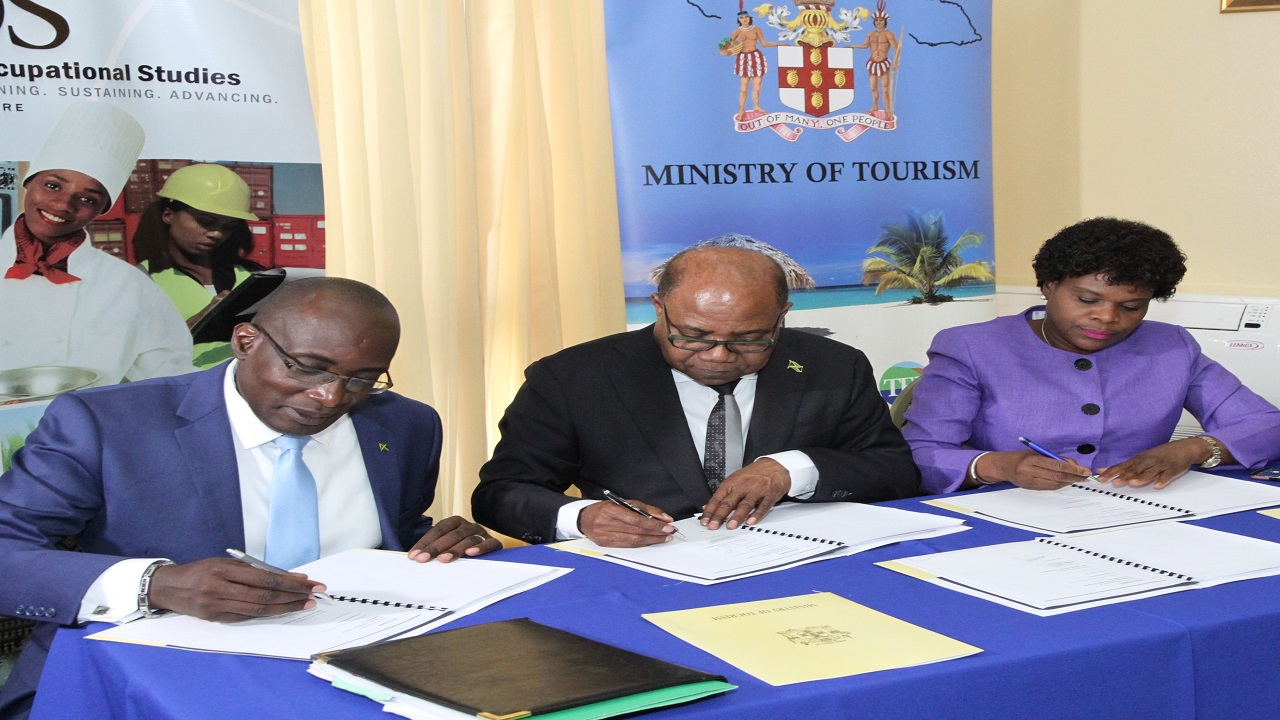 From left to right: Education Minister Senator Ruel Reid, Tourism Minister Edmund Bartlett and Permanent Secretary in the Ministry of Tourism Jennifer Griffith sign a Memorandum of Understanding (MOU) to initiate the first Hospitality and Tourism Management Programme for high school students to gain entry level qualification in tourism.
