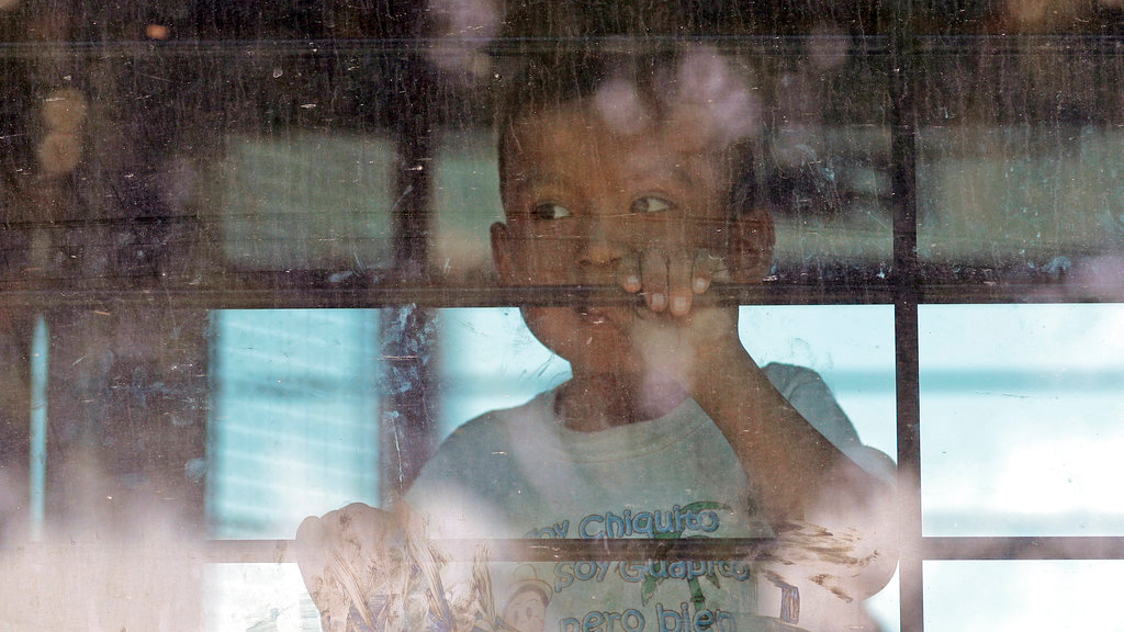 In this June 23, 2018, file photo, an immigrant child looks out from a U.S. Border Patrol bus leaving as protesters block the street outside the U.S. Border Patrol Central Processing Center in McAllen, Texas. Immigrant children described hunger, cold and fear in a voluminous court filing about the facilities where they were held in the days after crossing the border. (AP Photo/David J. Phillip, File)