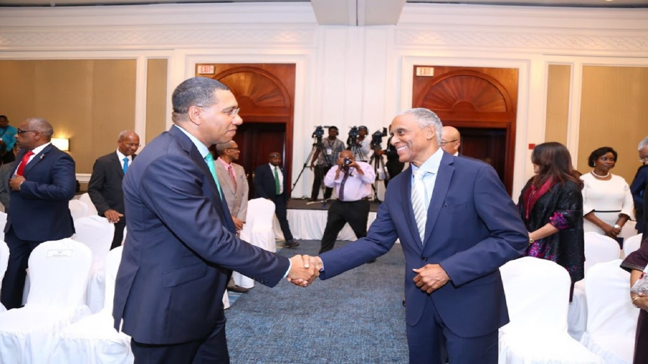 Jamaican Prime Minister Andrew Holness greets incoming President of the Caribbean Court of Justice, Justice Adrian Saunders during the Swearing-In Ceremony in  Montego Bay.