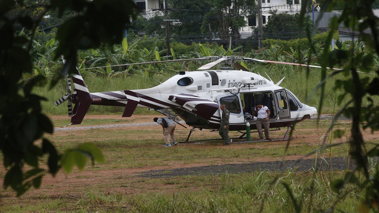 Two helicopters wait near the cave for more evacuations of the boys and their football coach who have been trapped since June 23, in Mae Sai, Chiang Rai province, northern Thailand Monday, July 9, 2018. Thailand's interior minister says the same divers who took part in Sunday's rescue of four boys trapped in a flooded cave will also conduct the next operation as they know the cave conditions and what to do. (AP Photo/Sakchai Lalit)