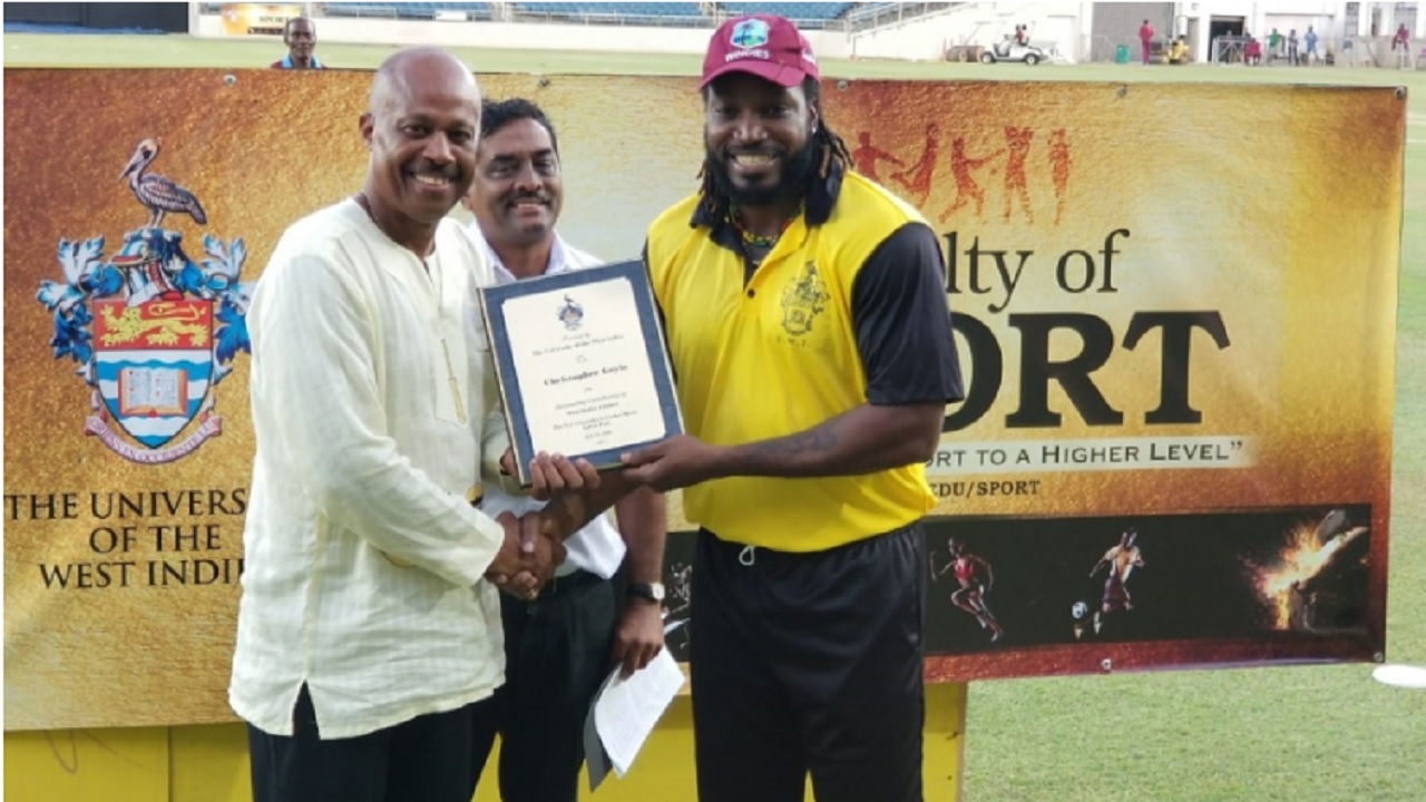 Chris Gayle (right) receives a plaque from University of the West Indies (UWI) Vice Chancellor Professor Hilary Beckles during the innings break of the one-off day/night 50-over match between a UWI Vice Chancellor's XI team and Bangladesh at Sabina Park. Dr.Akshai Mansingh, Dean of the Faculty of Sports at UWI, Mona looks on. Gayle and Patrick Patterson were honoured by the UWI for their contributions to cricket.