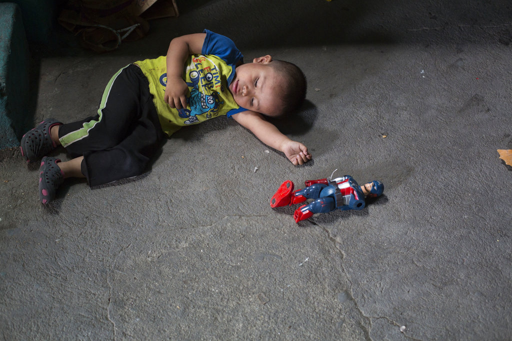 Isidro, the nephew of Paulina Gutierrez Alonzo, plays with a Captain America action figure. Gutierrez Alonzo was deported from United States in June and separated from her 7-year-old daughter Antonia Yolanda Gomez Gutierrez, Isidro's cousin, who is currently at an immigration center in Arizona.  (AP Photo/Moises Castillo)