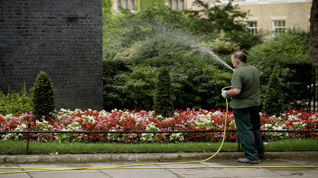 A worker uses a hose pipe to water flowers in Downing Street, London. (AP Photo)
