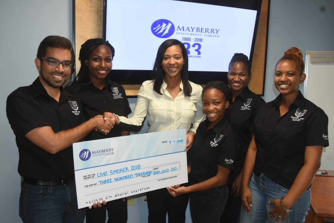 Anika Jengelley, Assistant VP of Marketing at Mayberry, (centre) hands over a symbolic cheque of $300,000 to the medical and dental students who are organising the production.