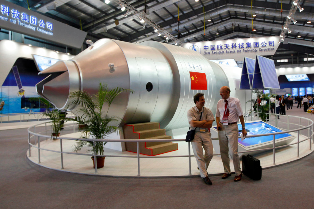 In this file photo, visitors sit beside a model of China's Tiangong-1 space station at the 8th China International Aviation and Aerospace Exhibition in Zhuhai in southern China's Guangdong Province. (AP Photo/Kin Cheung, File)