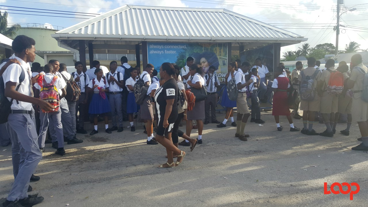 Students awaiting buses in Oistins.