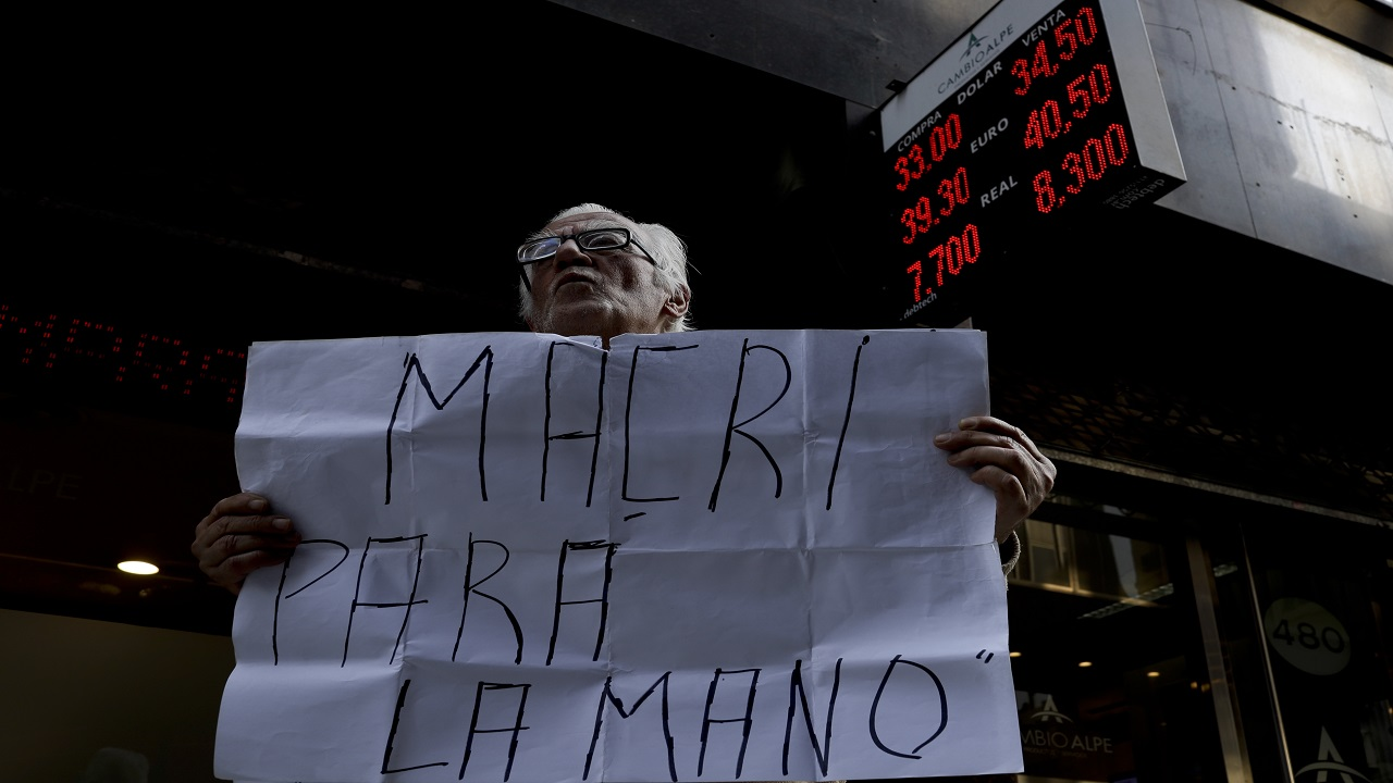 "A man with a sign reading in Spanish ""Stop Macri"" stands outside an exchange office in Buenos Aires, Argentina. (AP Photo)."