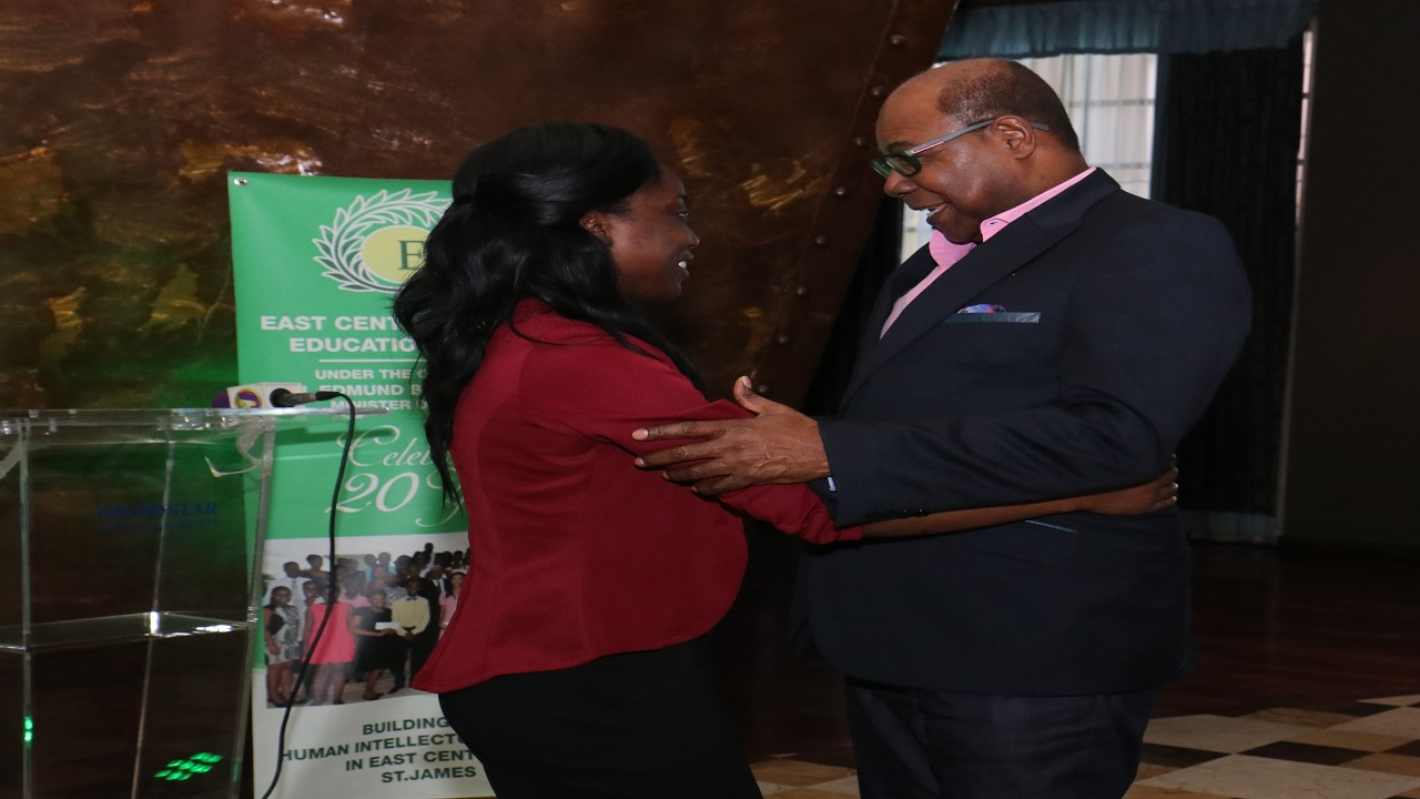 Member of Parliament for East Central St James Edmund Bartlett hugs NCU graduate Abby Gaye Gordon, a past beneficiary of the 2018 East Central St James Scholarship and Welfare Fund during the 2018 awards ceremony at the Iberostar Hotel in St James on Sunday.