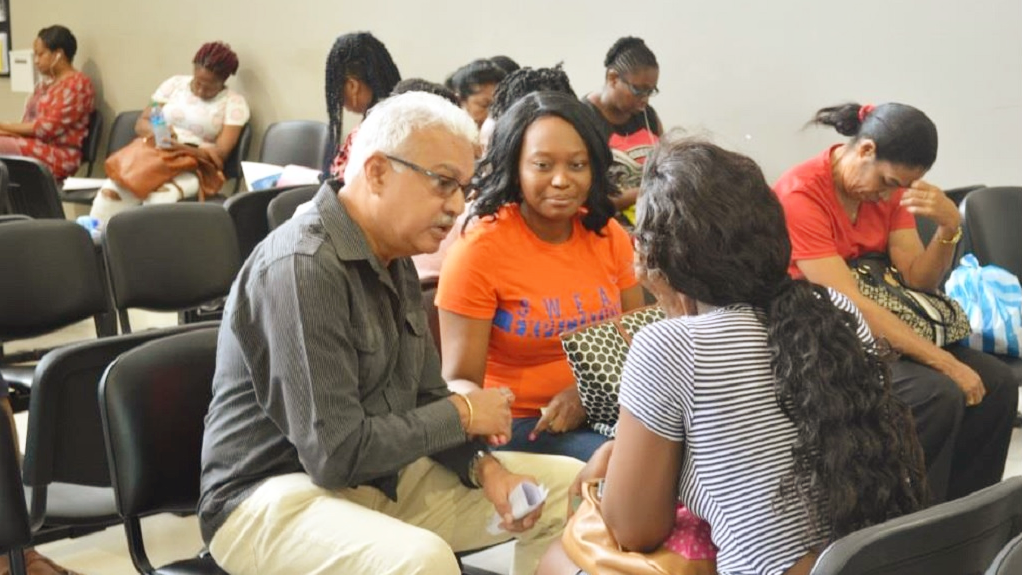 Photo: Health Minister, Terrence Deyalsingh speaks with some women awaiting screening during the Great Pap Smear Campaign on June 16.