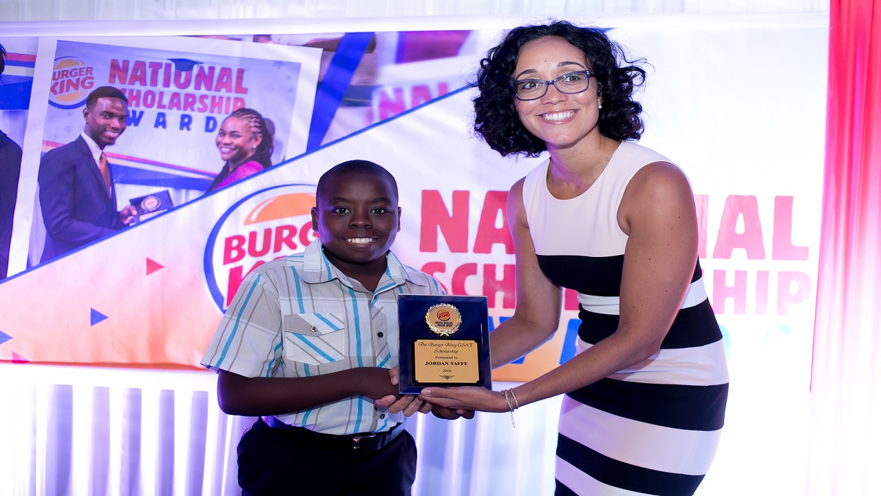 Jordan Taffe (left), one of seven recipients of Burger King Grade Six Achievement Text (GSAT) scholarships receives his award from Lisa Lake Epstein, Director, Burger King, at the presentation ceremony at the Terra Nova Hotel on Monday.