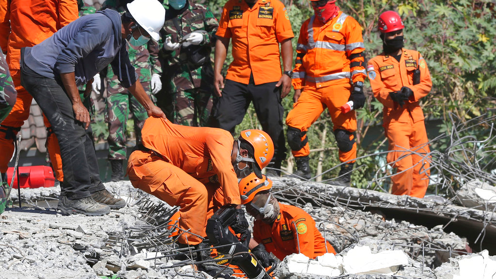 Rescuers carry the body of an earthquake victim recovered from the collapsed Jabal Nur mosque in North Lombok, Indonesia, Tuesday, Aug. 7, 2018. The north of Lombok was devastated by the powerful quake that struck Sunday night, damaging thousands of buildings and killing a large number of people.  (AP Photo/Tatan Syuflana)