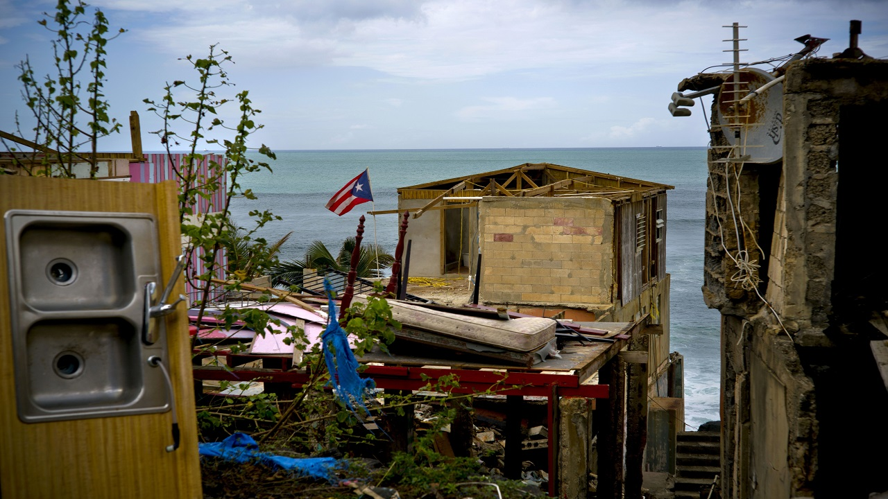 A Puerto Rican national flag is mounted on debris of a damaged home in the aftermath of Hurricane Maria in the seaside slum La Perla, San Juan, Puerto Rico. An independent investigation ordered by Puerto Rico's government estimates that nearly 3,000 people died as a result of Hurricane Maria. The findings issued Tuesday, Aug. 28, 2018, by the Milken Institute School of Public Health at George Washington University contrast sharply with the official death toll of 64. (AP Photo/Ramon Espinosa)