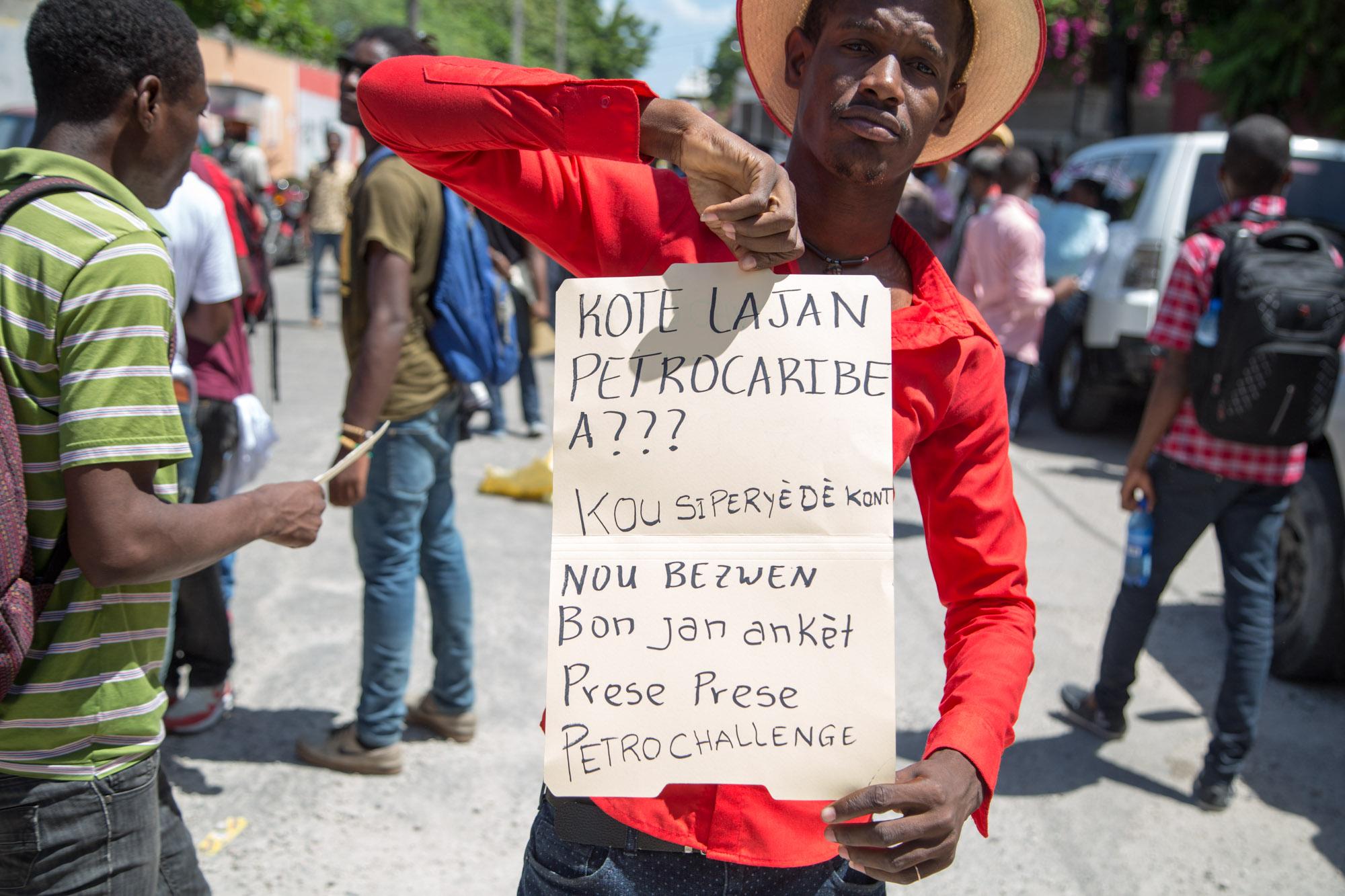 Un manifestant tenant une pancarte lors du sit-in devant les locaux de la cour supérieure des comptes à Port-au-Prince/ Photo: Estailove St-val/ LoopHaiti